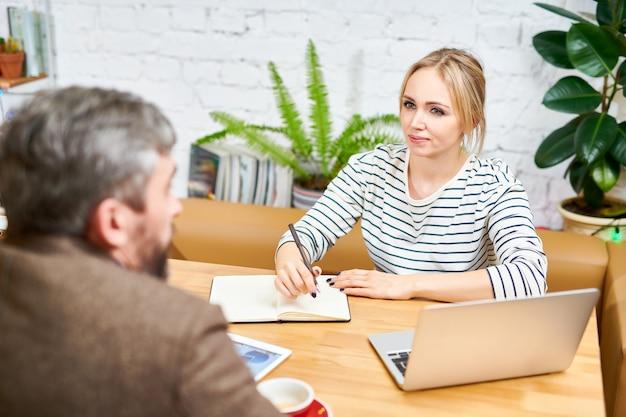 Giovane analista serio che prende appunti durante una conversazione di lavoro con un collega sullo sviluppo del business
