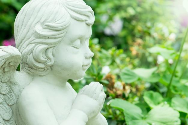 Giovane angel sculpture in giardino