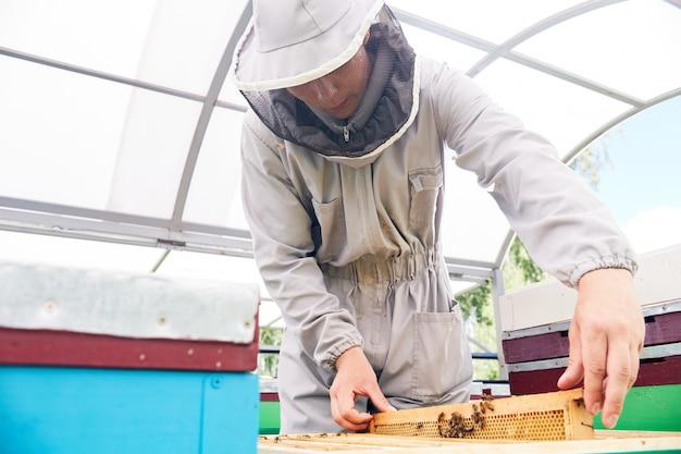 Giovane apicoltore in apiario