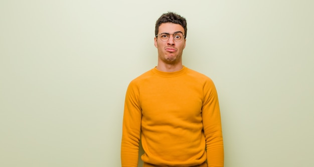 Giovane arabo che si sente triste e stressato, sconvolto a causa di una brutta sorpresa, con uno sguardo negativo e ansioso contro il muro piatto
