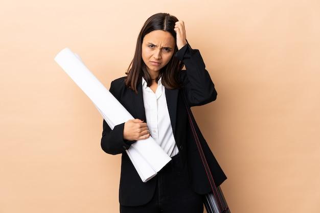 Giovane architetto donna con schemi sulla parete con un'espressione di frustrazione e non comprensione