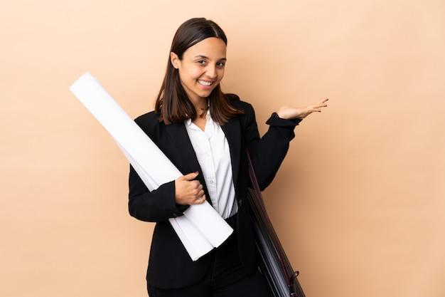 Giovane architetto donna in possesso di schemi sopra il muro che si estende le mani al lato per invitare a venire