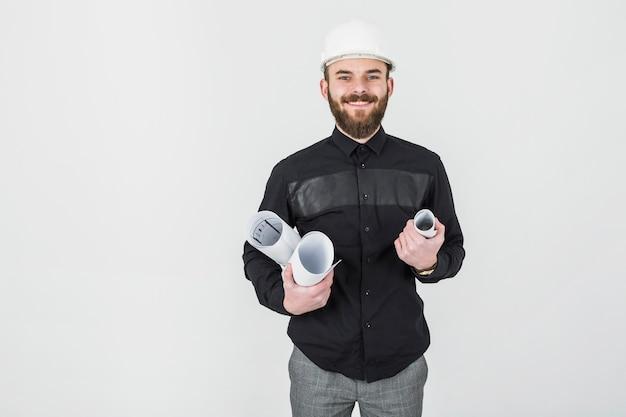 Giovane architetto maschio sorridente che tiene le stampe blu in sua mano