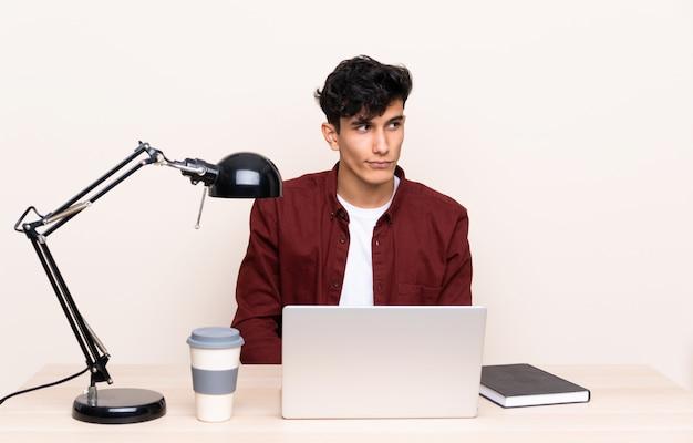 Giovane argentino in un tavolo con un computer portatile nel suo posto di lavoro in piedi e guardando al lato