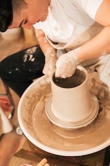 Giovane argilla da modellare femminile sorridente su un tornio da vasaio
