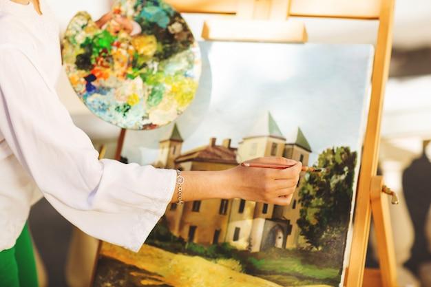 Giovane artista della donna del brunette che tiene in mani una spazzola e una gamma di colori. avvicinamento. concetto di arte