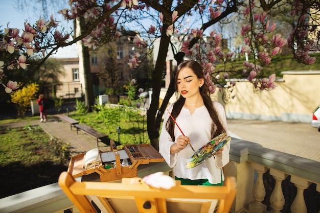 Giovane artista della donna del brunette che tiene in mani una spazzola e una gamma di colori.