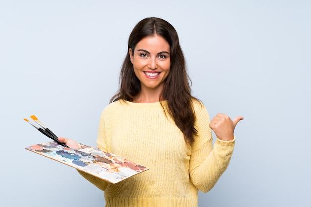 Giovane artista donna blu che punta verso il lato