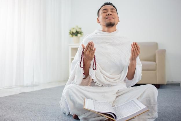 Giovane asiatico che prega con al-qur'an e le perle di preghiera