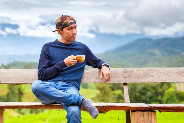 Giovane asiatico che sorride con il cappello che si siede su un banco di legno e che tiene tazza di caffè a tempo la mattina