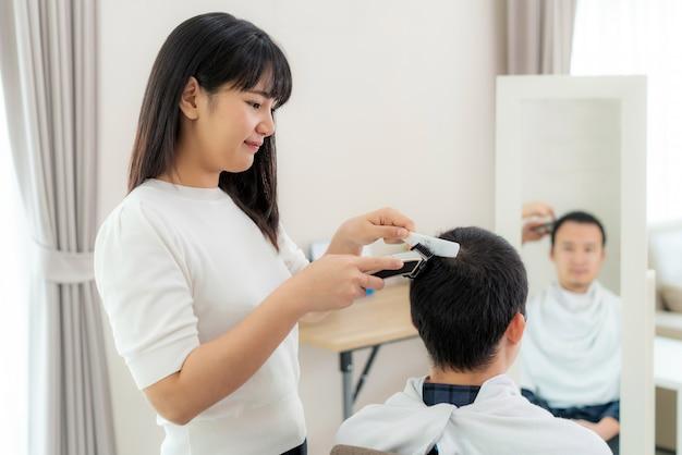 Giovane asiatico con la sua fidanzata parrucchiere che taglia i capelli con una tosatrice elettrica a casa restano a casa durante il periodo di isolamento domestico contro il nuovo coronavirus o covid-19