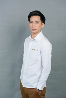 Giovane asiatico del ritratto su grey, adolescente