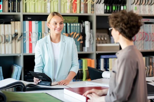 Giovane assistente femminile che consulta uno dei clienti mentre dà le sue idee dai cataloghi