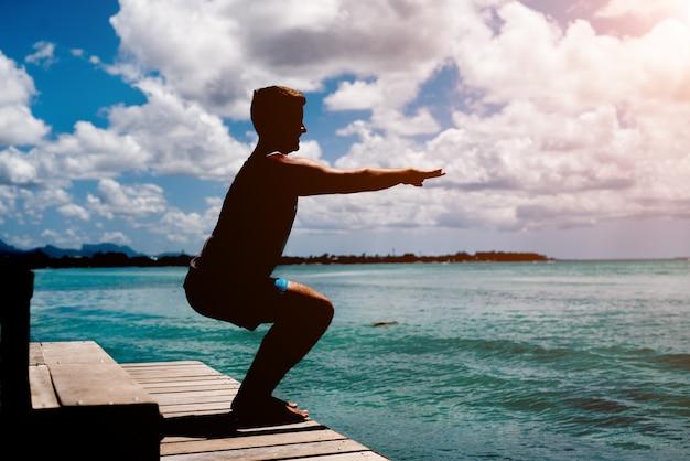 Giovane atleta che fa squat sul bacino del mare. sano stile di vita estivo.