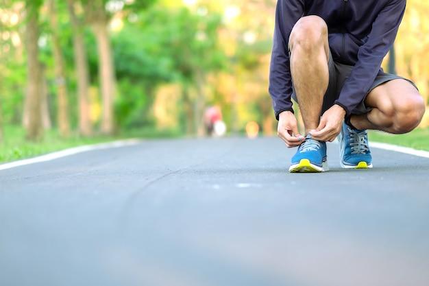 Giovane atleta che lega le scarpe da corsa nel parco all'aperto