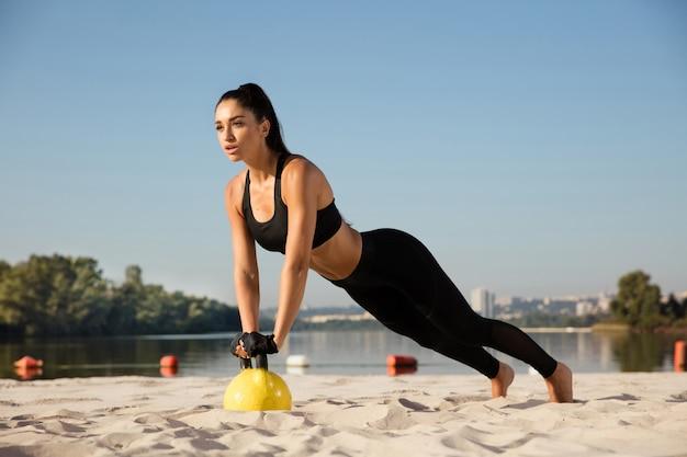 Giovane atleta femminile in buona salute facendo allenamento in spiaggia