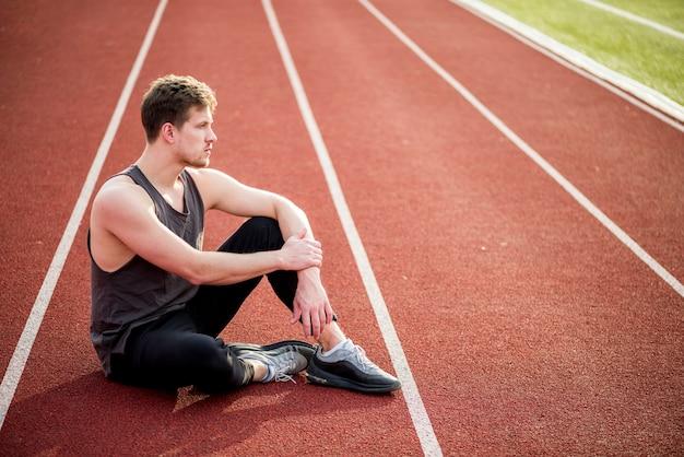 Giovane atleta maschio contemplato che si siede sulla pista di corsa