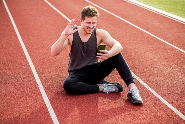 Giovane atleta maschio sorridente che si siede sulla pista di corsa rossa che ondeggia le sue mani mentre facendo videochiamata