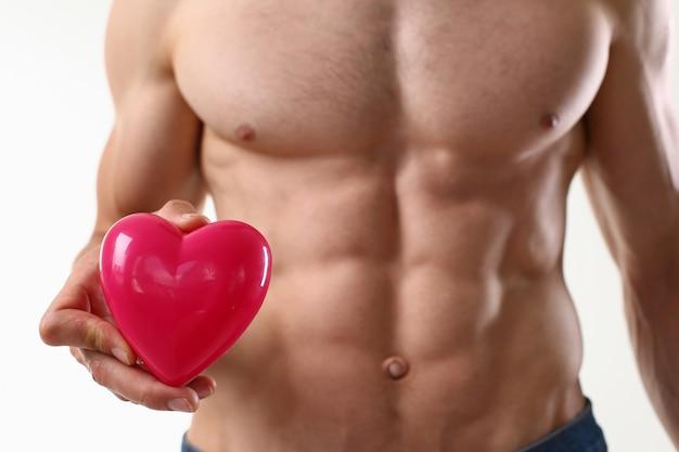 Giovane atletico con gli addominali perfetti che tengono cuore rosa