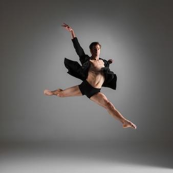 Giovane attraente ballerina moderna saltando su bianco