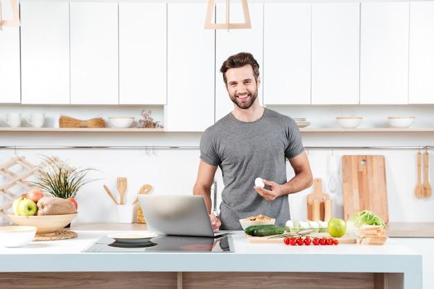 Giovane attraente che cucina con la ciotola mescolantesi