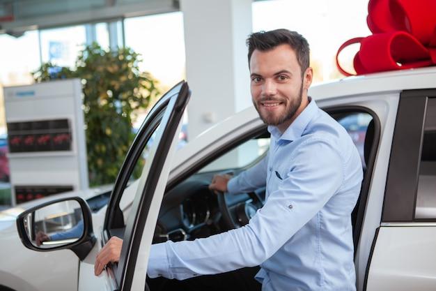 Giovane attraente che sorride alla macchina fotografica, mentre entrando in una nuova automobile da vendere alla concessionaria