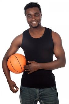 Giovane attraente con palla da basket su uno sfondo bianco