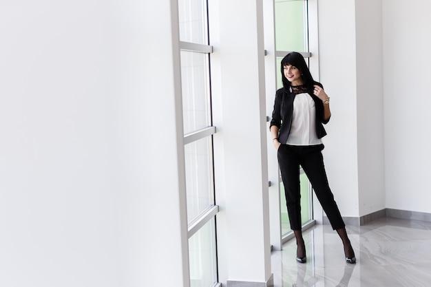 Giovane attraente donna bruna felice con i capelli lunghi in piedi vicino alla finestra in ufficio, sorridente, guardando fuori alla finestra.
