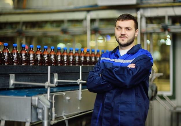 Giovane attraente maschio birraio o lavoratore birreria in uniforme sullo sfondo di un nastro trasportatore con bottiglie di plastica di birra