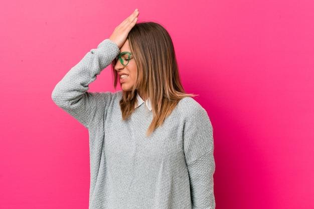 Giovane autentica carismatica gente vera donna contro un muro che dimentica qualcosa, schiaffeggiando la fronte con il palmo e chiudendo gli occhi.