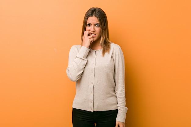 Giovane autentica carismatica gente vera donna contro un muro che morde le unghie, nervosa e molto ansiosa.