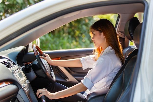 Giovane autista donna asiatica alla guida di un'auto sulla strada in campagna