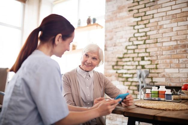 Giovane badante che insegna alla donna invecchiata per usare libro elettronico