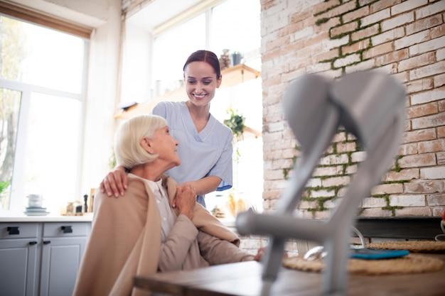 Giovane badante in uniforme che parla con il paziente