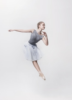Giovane ballerina classica danza su sfondo bianco. progetto ballerina.
