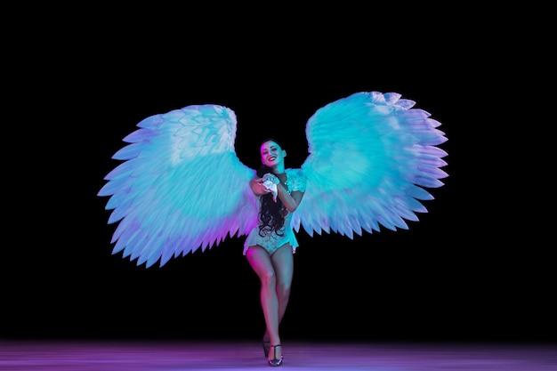 Giovane ballerina con ali d'angelo in luce al neon sul muro nero