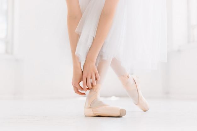 Giovane ballerina di danza, primo piano su gambe e scarpe, in piedi in posizione di punta.