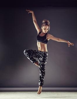 Giovane ballerina donna sottile in abbigliamento sportivo salto in alto sul fondo della parete