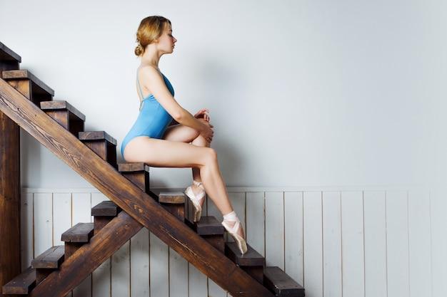 Giovane ballerina femminile in abito blu, seduto sulle scale
