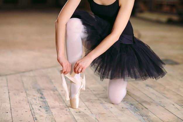 Giovane ballerina in abito nero si allena dietro le quinte.