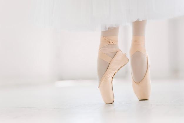 Giovane ballerina, primo piano su gambe e scarpe, in piedi in posizione di punta.
