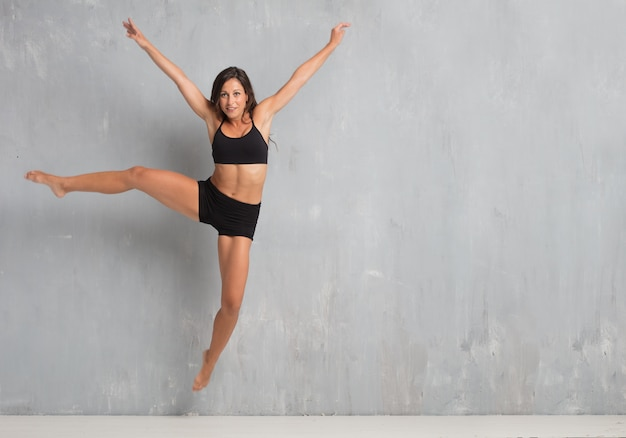 Giovane ballerino della via della donna graziosa che salta contro il bac della parete di lerciume
