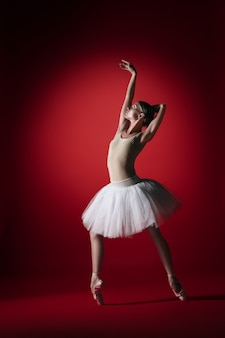 Giovane ballerino di balletto femminile grazioso o ballerina classica che balla allo studio rosso.