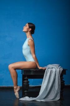 Giovane ballerino di balletto moderno che posa sul blu