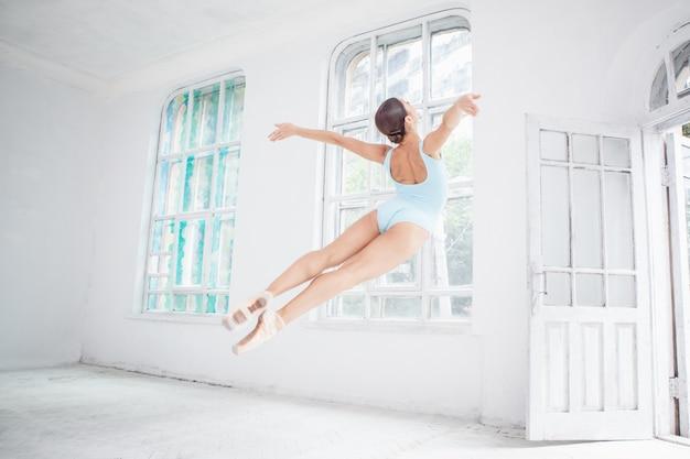 Giovane ballerino di balletto moderno che salta sulla parete bianca