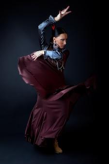 Giovane ballerino di flamenco in bel vestito su sfondo nero.
