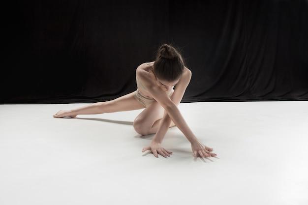 Giovane ballerino teenager che balla sul fondo bianco dello studio del pavimento. progetto ballerina.