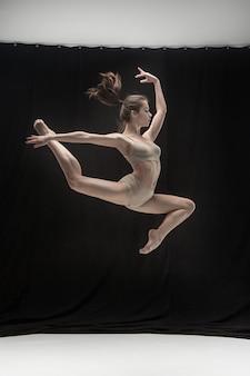 Giovane ballerino teenager sullo spazio bianco del pavimento.