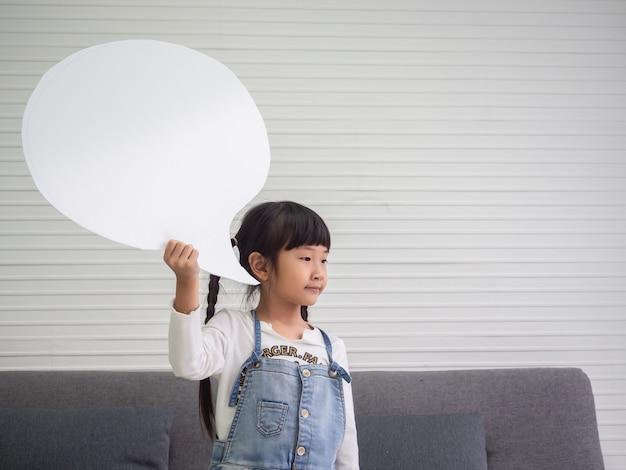 Giovane bambina asiatica che tiene un segno in bianco