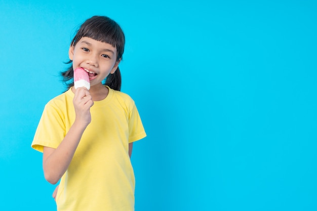 Giovane bambino asiatico della ragazza che mangia il gelato e pubblicazione divertente